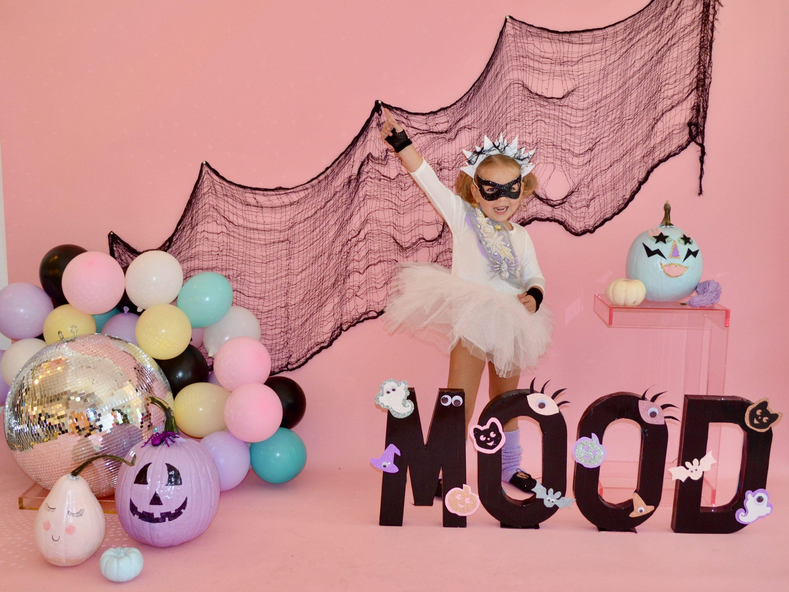Adorable preschool dancer on a pastel Halloween background