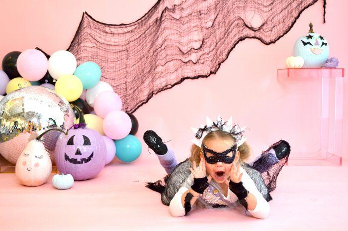 Preschool dancer wearing bat mask, posing in front of pastel halloween decor