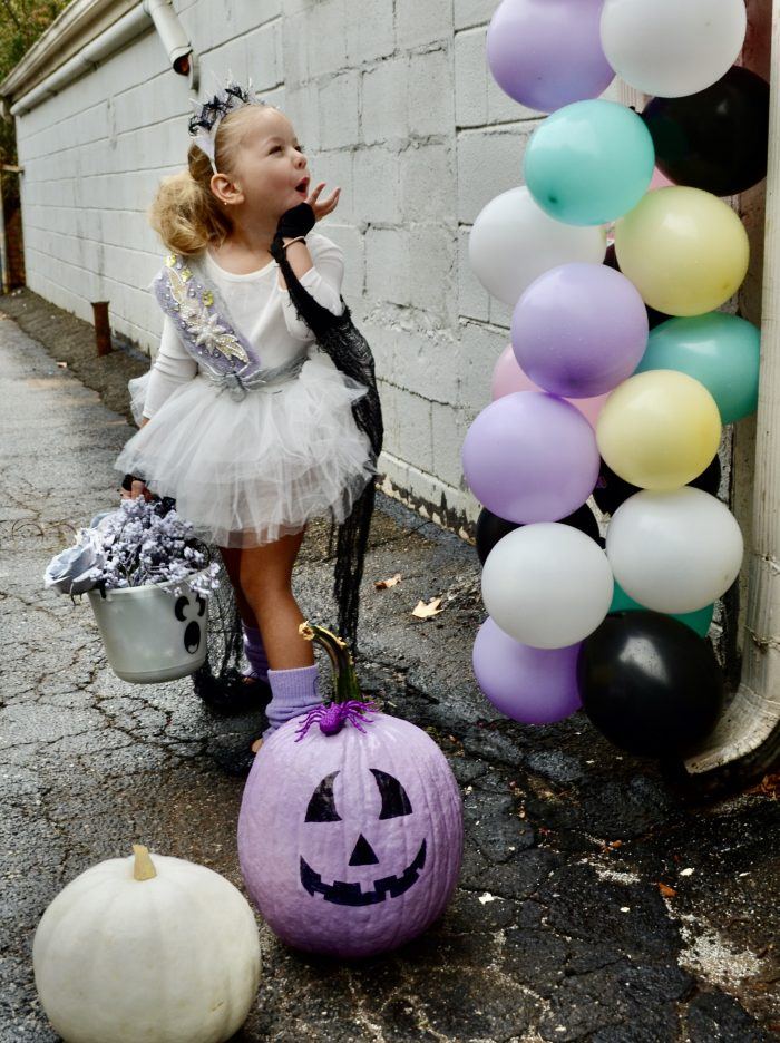 Adorable preschool dancer in white tutu dressed up for trick or treating next to pastel jack-o-lantern and balloon garland.