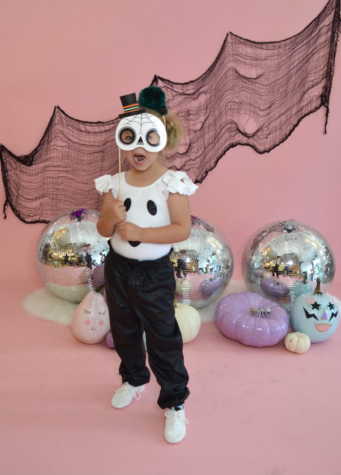 Preschool dancer wearing ghost leotard posing in front of Halloween decor and disco balls while holding a skeleton photo prop over face.