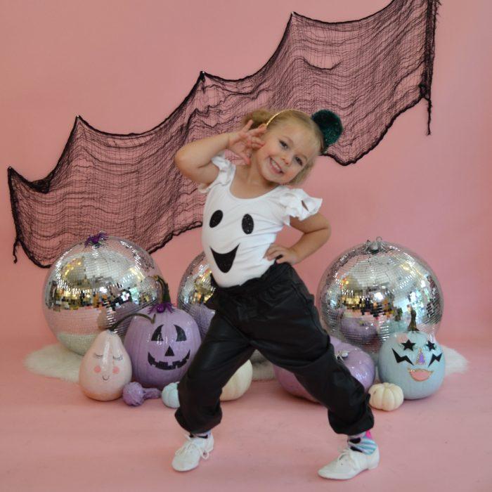Preschool dancer wearing ghost leotard posing in front of Halloween decor and disco balls