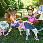 Two young dancers posing in a woodlands scene with disco balls and a sparkly mushroom, getting ready for a fun dance activity!