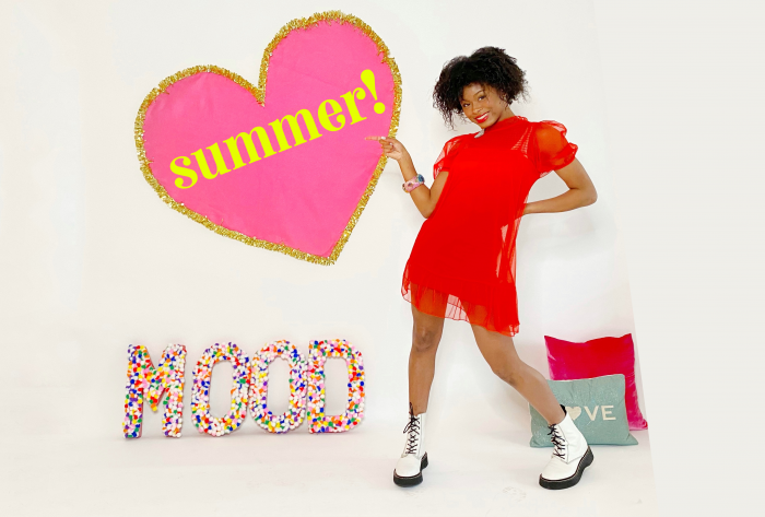 Dancer posing in red dress next to letters that spell out MOOD and pointing to a heart on the wall with the word summer inside it.