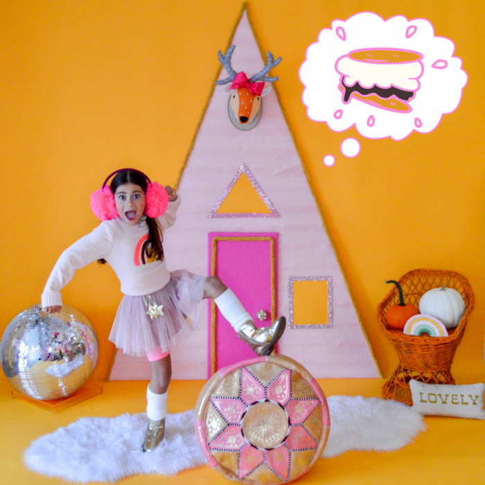 Cut young girl wearing giant earmuffs dreaming of s'mores on a pastel background.